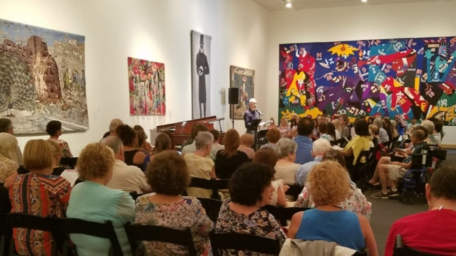 Photo taken from behind a crowded, seated audience in an art gallery. On the farthest wall, a colorful geometric painting. A man stands at a microphone in the centre of the room.