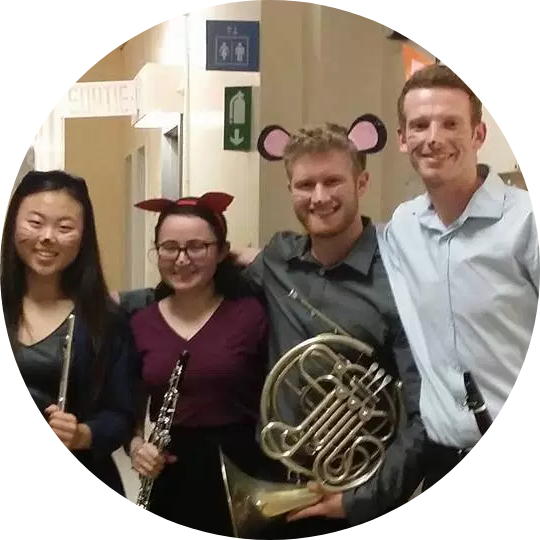 From left to right, a flute player, oboe player, French horn player, and clarinet player stand together smiling at the camera and holding their instruments. They wear headbands with cartoon animal ears, and have whiskers painted on their faces.